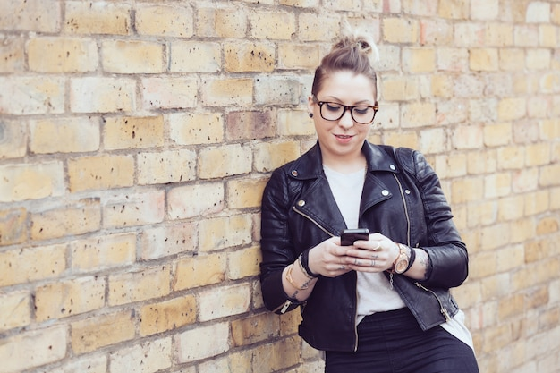 Donna dei pantaloni a vita bassa che scrive sullo smart phone a londra.