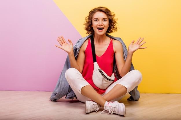 Donna dei pantaloni a vita bassa con il fronte di sorpresa che posa nello studio sul rosa e sul giallo.