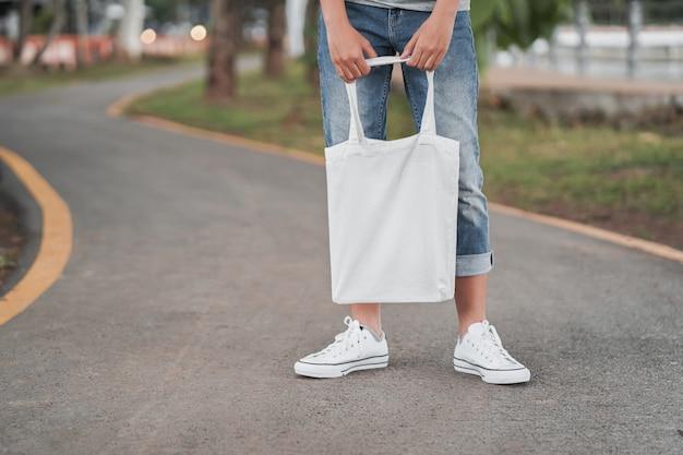 Donna dei pantaloni a vita bassa con la borsa di cotone bianca sulla strada