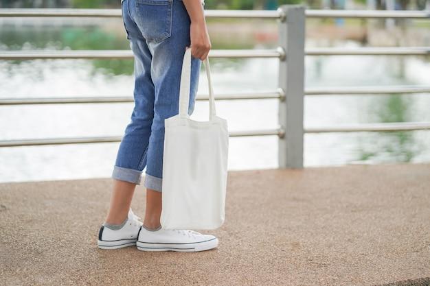 Donna dei pantaloni a vita bassa con la borsa di totalizzatore bianca nel parco