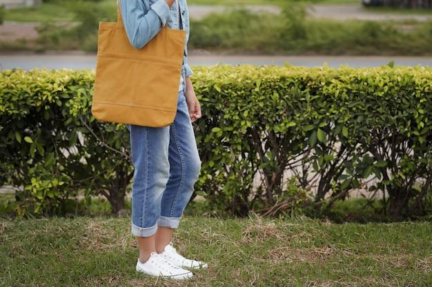 Donna dei pantaloni a vita bassa con la borsa di totalizzatore gialla su erba verde