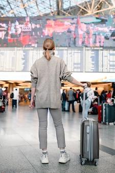 Donna dei viaggiatori che cammina con un bagaglio al terminal dell'aeroporto
