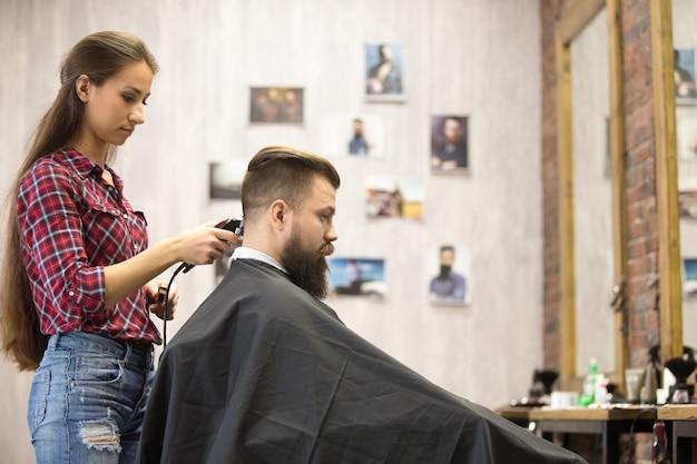 Donna del barbiere che serve cliente in barbiere