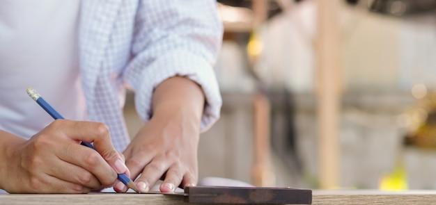 Donna del carpentiere che usando righello per misurare sul legname a casa