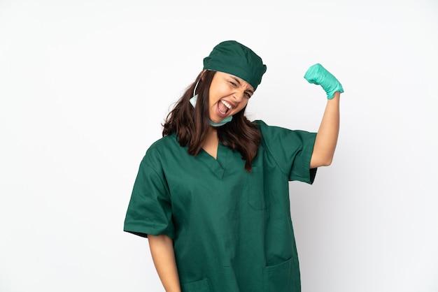 Donna del chirurgo in uniforme verde sulla parete bianca che fa forte gesto