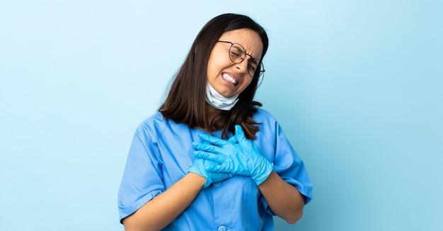 Donna del chirurgo sopra la parete blu che ha un dolore nel cuore