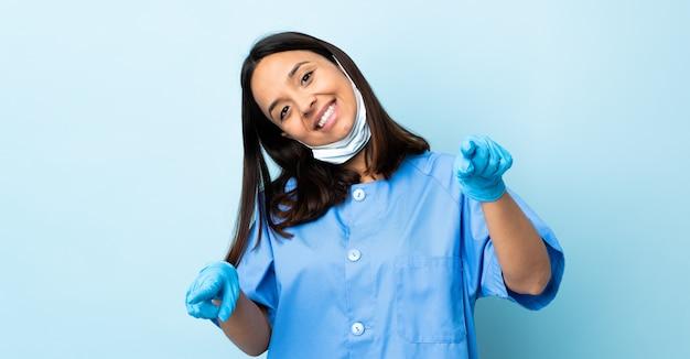 Donna del chirurgo sopra la parete blu isolata che indica parte anteriore con l'espressione felice