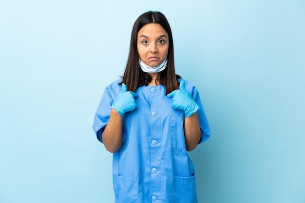 Donna del chirurgo sopra la parete blu isolata con espressione facciale di sorpresa