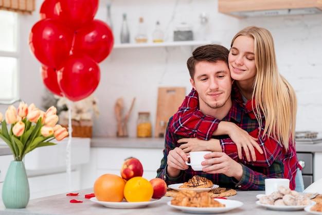 Donna del colpo medio che abbraccia uomo nella cucina
