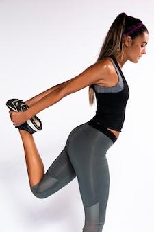 Donna del colpo medio che allunga la sua gamba