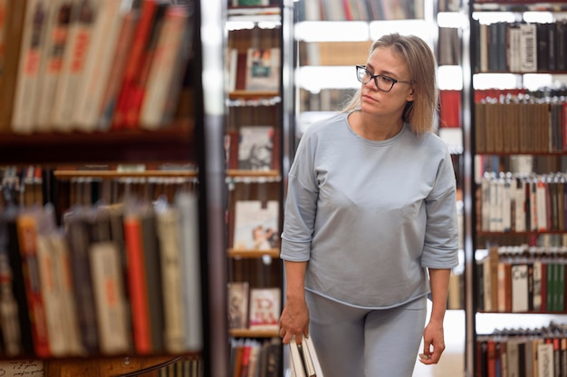 Donna del colpo medio che cammina nella libreria