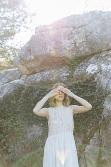 Donna del colpo medio che copre gli occhi di mani