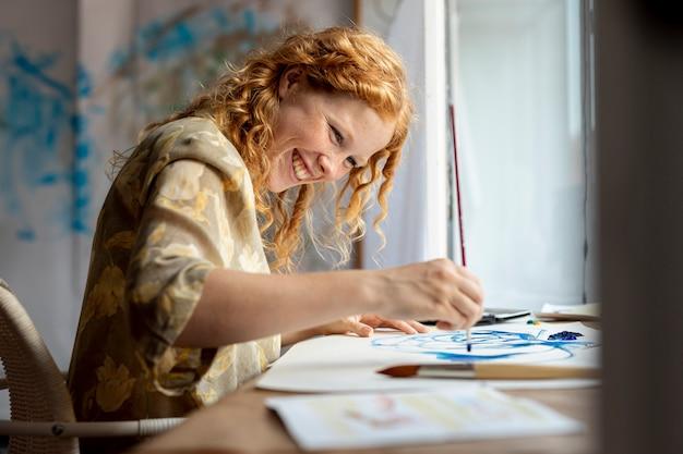 Donna del colpo medio che dipinge felicemente