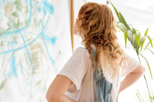 Donna del colpo medio che esamina una parete