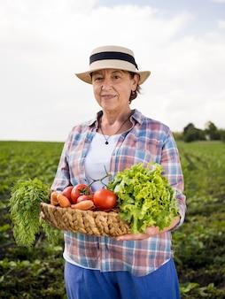 Donna del colpo medio che giudica un canestro pieno delle verdure