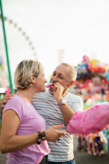 Donna del colpo medio che mangia zucchero filato rosa