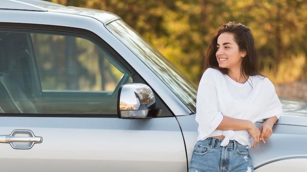 Donna del colpo medio che posa vicino all'automobile
