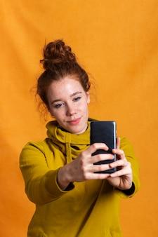 Donna del colpo medio che prende un selfie con fondo arancio