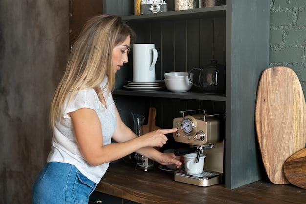 Donna del colpo medio che produce caffè