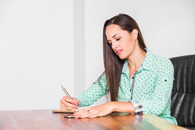 Donna del colpo medio che si siede e che scrive