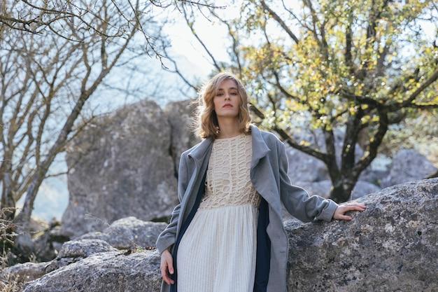 Donna del colpo medio che si siede vicino alle rocce