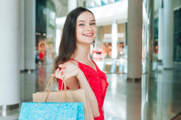 Donna del colpo medio che sorride al centro commerciale