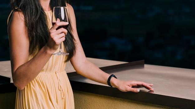 Donna del colpo medio che tiene bicchiere di vino
