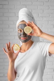 Donna del colpo medio che tiene le fette di limone