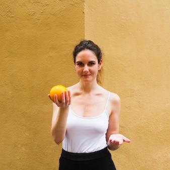 Donna del colpo medio che tiene un'arancia