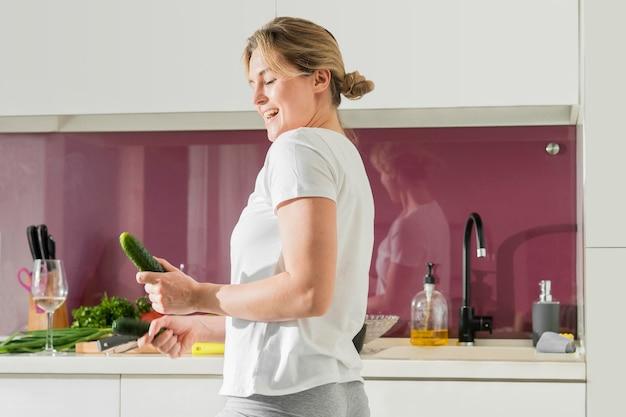 Donna del colpo medio che tiene un cetriolo nella cucina