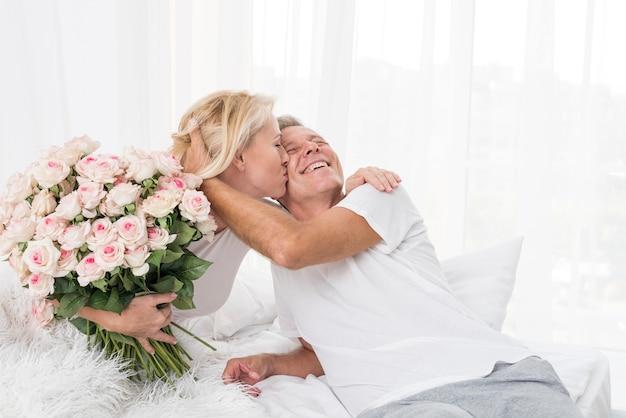Donna del colpo medio con i fiori che baciano uomo