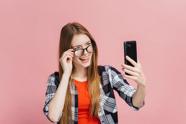 Donna del colpo medio con i vetri che prendono un selfie