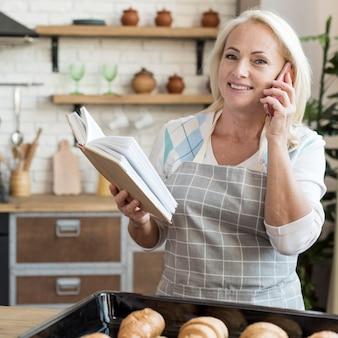 Donna del colpo medio con il libro che parla sul telefono