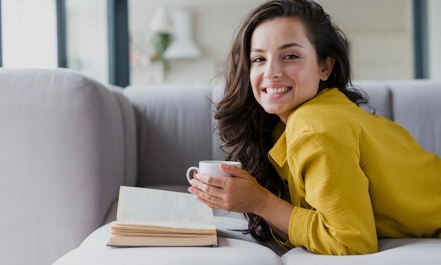 Donna del colpo medio sul sofà con il libro e la tazza