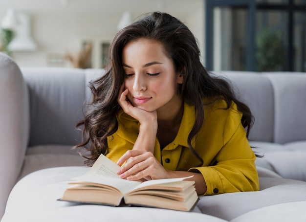 Donna del colpo medio sulla lettura del sofà