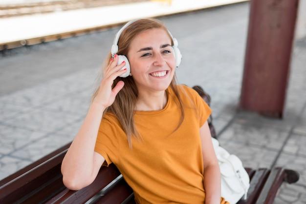 Donna del colpo metà che ascolta la musica sulla panchina nella stazione ferroviaria
