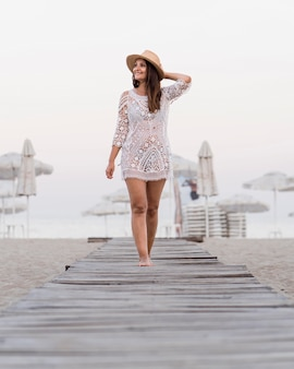 Donna del colpo pieno che posa alla spiaggia