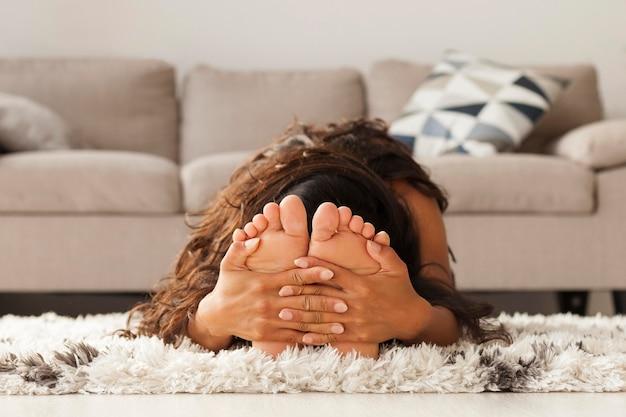 Donna del colpo pieno che si estende sul tappeto