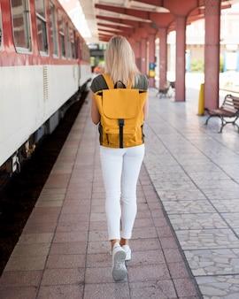 Donna del colpo pieno con lo zaino che cammina nella stazione ferroviaria