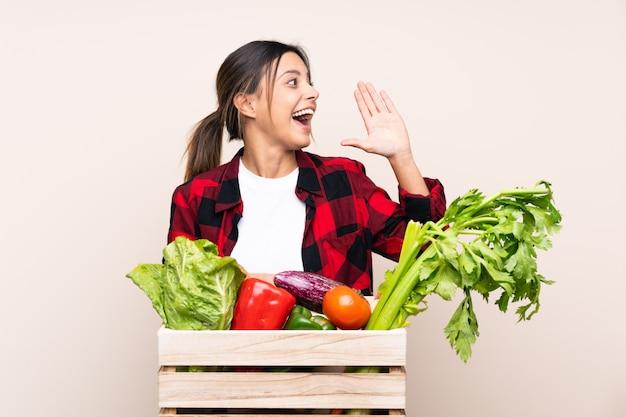 Donna del coltivatore che tiene gli ortaggi freschi in un canestro di legno che grida con la bocca spalancata