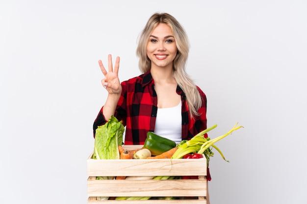Donna del coltivatore con scatola di verdure