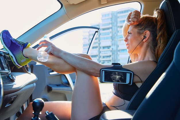 Donna del corridore che si rilassa dopo l'allenamento dentro l'automobile