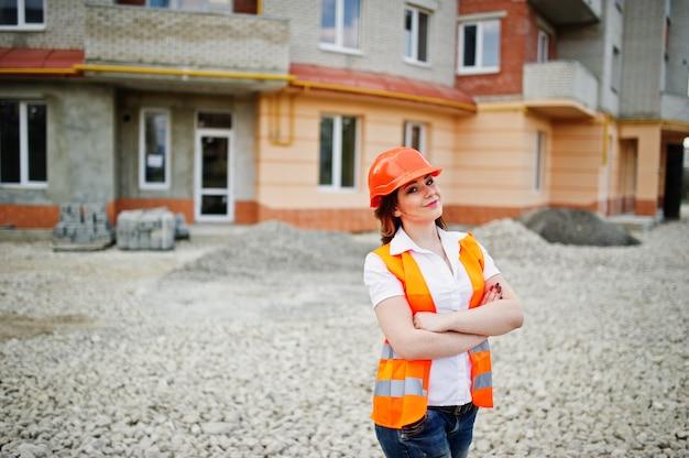 Donna del costruttore dell'ingegnere in panciotto uniforme e casco protettivo arancio contro la nuova costruzione