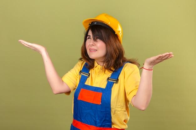 Donna del costruttore in uniforme di costruzione e casco di sicurezza che scrolla le spalle le spalle allargando le mani non capendo cosa è successo espressione confusa e confusa sopra la parete verde isolata