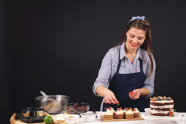 Donna del cuoco unico di pasticceria che decora una torta su una priorità bassa isolata