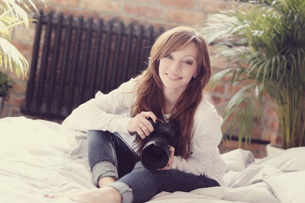 Donna del fotografo che si trova nel letto con la macchina fotografica