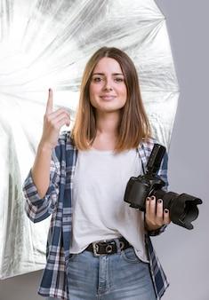 Donna del fotografo che tiene una macchina fotografica professionale