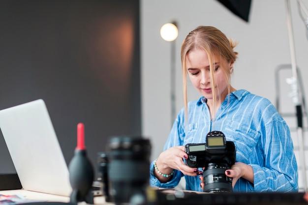 Donna del fotografo e la sua lente che stanno al suo scrittorio