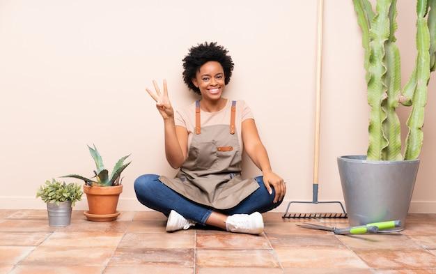 Donna del giardiniere che si siede sul pavimento