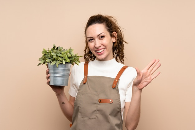 Donna del giardiniere che tiene una pianta che saluta con la mano con l'espressione felice